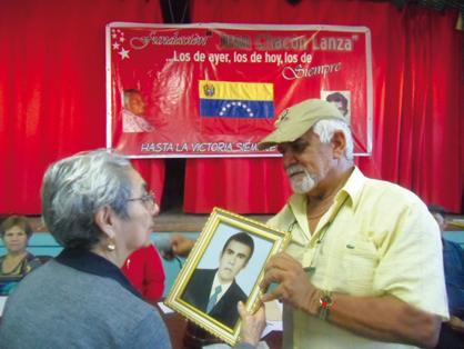 Zenaida, la madre de Rodríguez, recibe de Omar Narváez una pintura de su hijo en un acto realizado en El Tigre. Foto: CiudadCCS