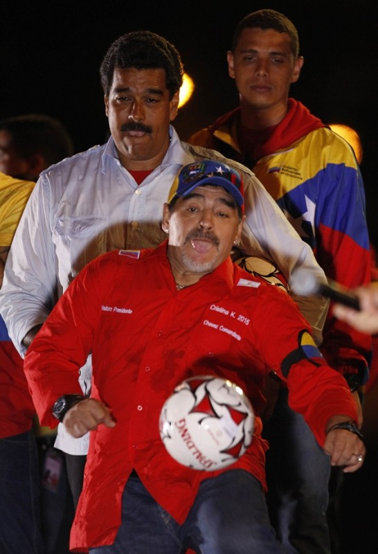 Venezuela's acting President and presidential candidate Maduro watches former Argentine soccer star Maradona kick a ball during his closing campaign rally in Caracas