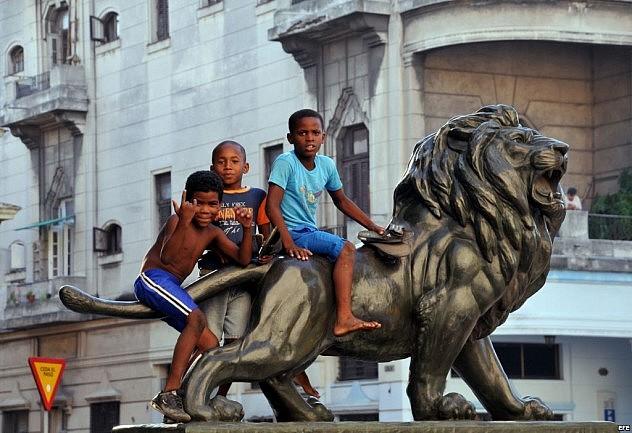 Niños juegan sobre uno de los leones del Paseo del Prado de La Habana (Foto: Agencias)