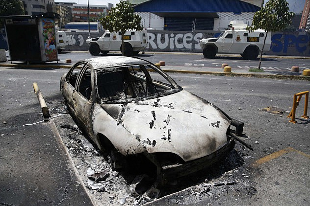 National guard armored vehicles drives past a burnt vehicle after riots in Caracas