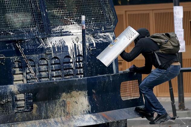 """Opositor se trepa en una unidad antimotines de la PNB, conocida como """"la ballena"""". Foto: Jorge Silva, Reuters"""