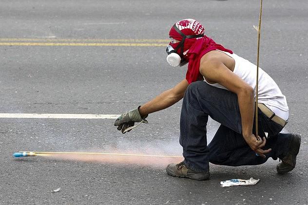 Opositore lanza cohetones contra la PNB en el distribuidor Santa fe este lunes. Nótese la franela en la cabeza. Foto: Christian Veron, Reuters (Fuente)