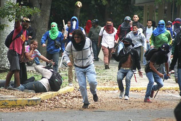 Jóvenes en primer plano huyen tras haber brindado una gopiza a otro estudiante que estaba en el piso. Foto: Rafael Hernández, Demotix