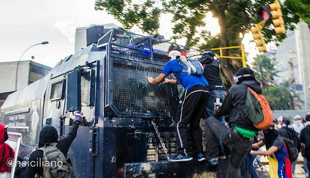 """Opositor se trepa en una unidad antimotines de la PNB, conocida como """"la ballena"""". El conductor fue forzado a retroceder pues sería culpable penalmente si algo le ocurría a los manifestantes que se trepaban en el vehículo. Foto: Horacio Siciliano"""