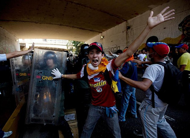 Algunos opositores llamaron a sus compañeros a no atacar a un grupo pequeño de efectivos de la Guardia Nacional Boliuvariana, que quedó atrapado entre dos grandes grupos de opositores debajo de un elevado en Bello Monte. Otros opositores llamaban a atacarlos. Foto: Fernando Llano, AP