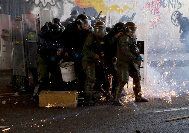 Un grupo de efectivos de la Guardia Nacional Bolivariana se protegen del ataque con cohetones de parte de opositores en Bello Monte. Foto: Fernando Llano, AP