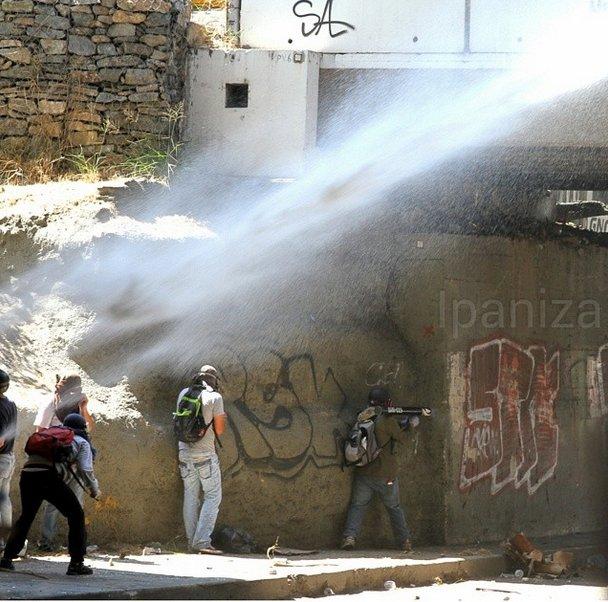 """En Bello Monte. Foto: Isaac Paniza. Su leyenda: """"Mientras unos reciben agua otro se prepara para dar fuegos artificiales"""""""