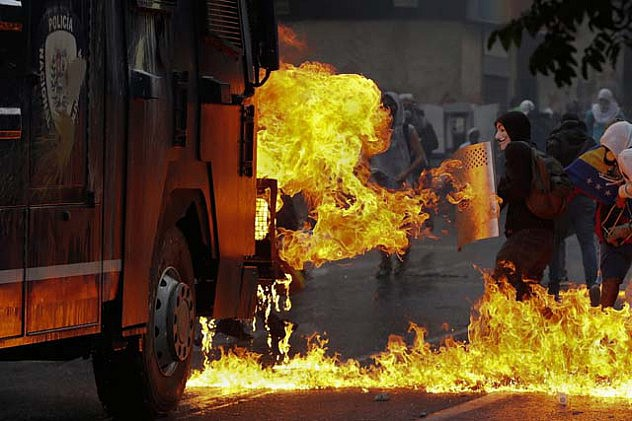 An anti-government protester stands with a shield near flames from molotov cocktails thrown at a water cannon by anti-government protesters during riots in Caracas