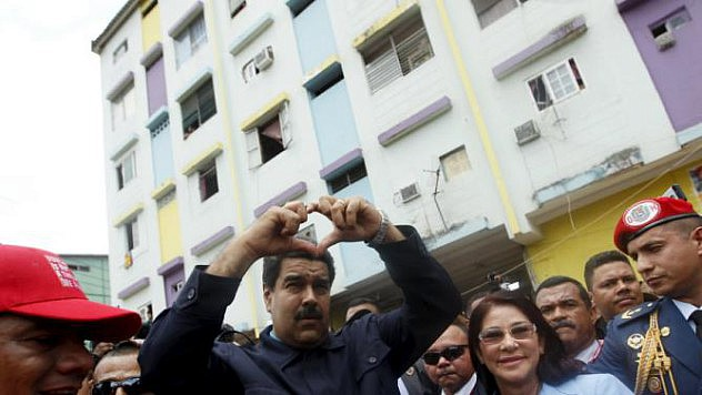 Venezuela's President Nicolas Maduro next to his wife Cilia Flores forms a heart shape with his hands during a visit to the working-class neighbourhood El Chorrilo, which was bombed during the 1989-U.S. invasion, in Panama City