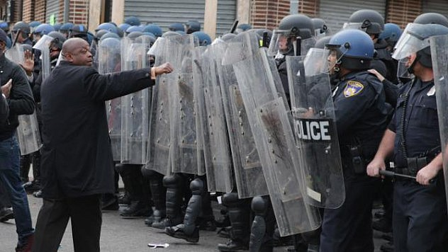BALTIMORE, MD - APRIL 27:  A demonstrator faces off with a line of Baltimore Police officers at the corner of Pennsylvania and North avenues during violent protests following the funeral of Freddie Gray April 27, 2015 in Baltimore, Maryland. Gray, 25, who was arrested for possessing a switch blade knife April 12 outside the Gilmor Homes housing project on Baltimore's west side. According to his attorney, Gray died a week later in the hospital from a severe spinal cord injury he received while in police custody.  (Photo by Chip Somodevilla/Getty Images)
