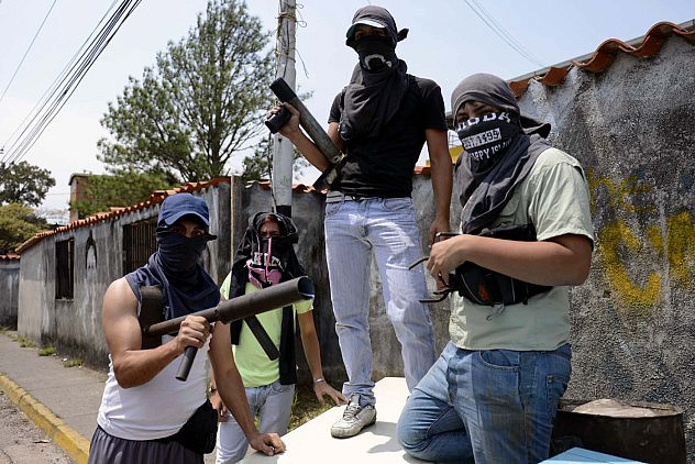 Anti-government activists pose for a picture on a barricade in San Cristobal, Tachira state, on March 6, 2014. A police officer and a civilian died Thursday during clashes in the Venezuelan capital Caracas, bringing to 20 the toll from a month of anti-government demonstrations in the divided country. AFP PHOTO/Leo RAMIREZ
