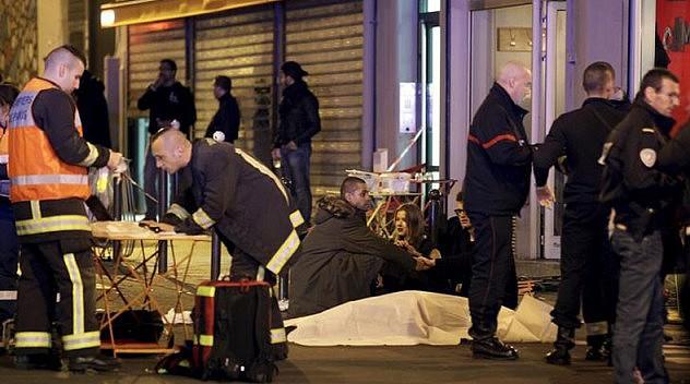 Socorristas en la escena de un tiroteo en París, nov 13, 2015.  Al menos 18 personas murieron el viernes en tiroteos en el centro de París y se escucharon explosiones cerca de un estadio donde se jugaba un partido de selecciones de fútbol, reportaron la cadena de televisión francesa BFM TV y otros medios.. ATENCIÓN EDITORES: IMAGEN CON COBERTURA VISUAL DE HERIDOS O MUERTOS      REUTERS/Philippe Wojazer