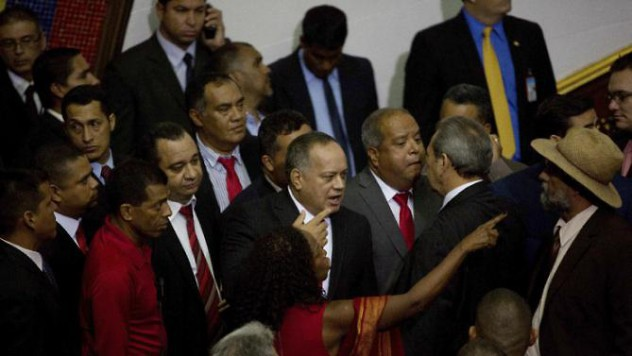 Diosdado Cabello, outgoing parliamentary president, center, and fellow legislators walk out in protest from the National Assembly in Caracas, Venezuela, Tuesday, Jan. 5, 2016. Venezuela's opposition was sworn in Tuesday as the majority in the National Assembly. The lawmakers were sworn in during a heated parliamentary session that saw pro-government representatives walk out in protest after pushing and shoving their way onto the dais as the new leadership laid out its legislative agenda. (AP Photo/Fernando Llano)