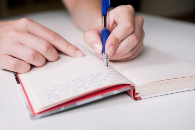 Mujer-sosteniendo-un-boligrafo-en-su-mano-y-escribiendo-en-su-diario-sobre-una-mesa-blanca
