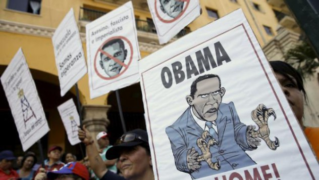 Supporters of Venezuela's President Nicolas Maduro hold placards depicting U.S. President Barack Obama during a rally in Caracas, March 12, 2016. REUTERS/Carlos Garcia Rawlins