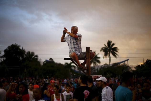 A fan takes a photograph while sitting on a pole before a free outdoor concert by the Rolling Stones at the Ciudad Deportiva de la Habana sports complex in Havana, Cuba March 25, 2016. REUTERS/Ivan Alvarado