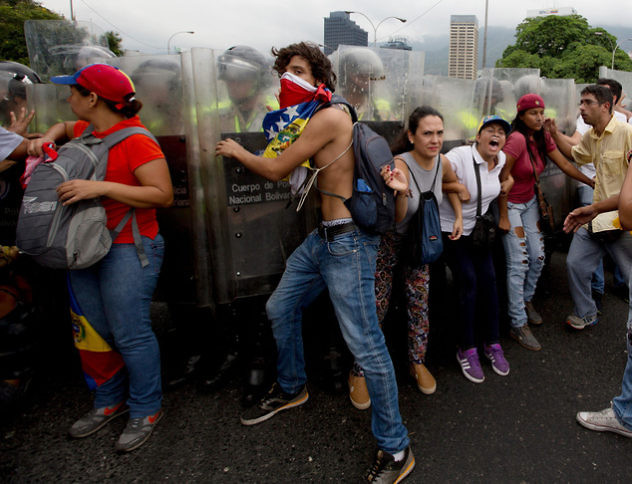 Anti-government demonstrators push against Bolivarian National Police blocking them from reaching the National Electoral Council (CNE) in Caracas, Venezuela, Wednesday, May 11, 2016. The opposition is marching to demand election officials start counting signatures that could lead to a presidential recall vote. (AP Photo/Fernando Llano)