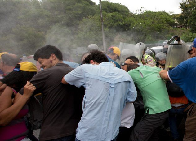 Venezuelans react to the effects of pepper gas after riot police fired the gas to repel marchers protesting against the government, in Caracas, Venezuela, Wednesday, May 11, 2016. Thousands are marching against the country's socialist administration, demanding that elections officials start counting signatures that could lead to a presidential recall vote. On Wednesday, law enforcement cordoned off the electoral building opposition leaders had planned to march to. Opposition leader Henrique Capriles is pictured in baseball cap, back center. (AP Photo/Fernando Llano)
