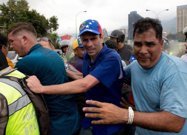 Opposition leader Henrique Capriles, center, reacts to the effects of pepper gas as he is led away by his bodyguards after soldiers fired the gas to repel marchers protesting against the government, in Caracas, Venezuela, Wednesday, May 11, 2016. (AP Photo/Fernando Llano)Thousands of Venezuelans are marching against the country's socialist administration, demanding that elections officials start counting signatures that could lead to a presidential recall vote. (AP Photo/Fernando Llano)