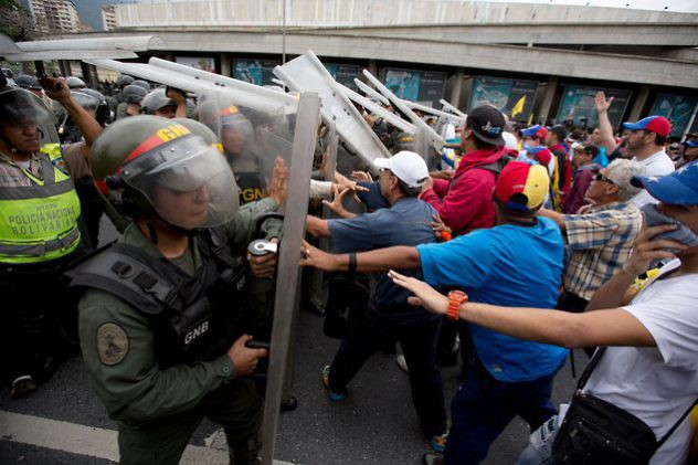 Anti-government demonstrators push against Bolivarian National Guard soldiers blocking their march to the National Electoral Council (CNE) in Caracas, Venezuela, Wednesday, May 11, 2016. The opposition is marching to demand election officials start counting signatures that could lead to a presidential recall vote. (AP Photo/Fernando Llano)
