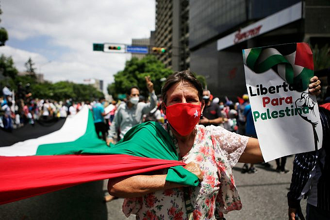 """A woman holds a Palestinian flag and a sign that reads: """"Freedom for Palestine"""" during a mobilization in favor of the Palestinian people, in Caracas, Venezuela, on Tuesday, May 25, 2021. Photo: Jesús Vargas, AVN"""