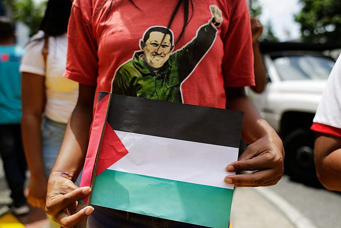 A young woman dressed in a shirt of the late Venezuelan president, Hugo Chávez, holds a Palestinian flag during a march in favor of the Palestinian people, in Caracas, Venezuela, on Tuesday, May 25, 2021. Photo: Jesús Vargas, AVN